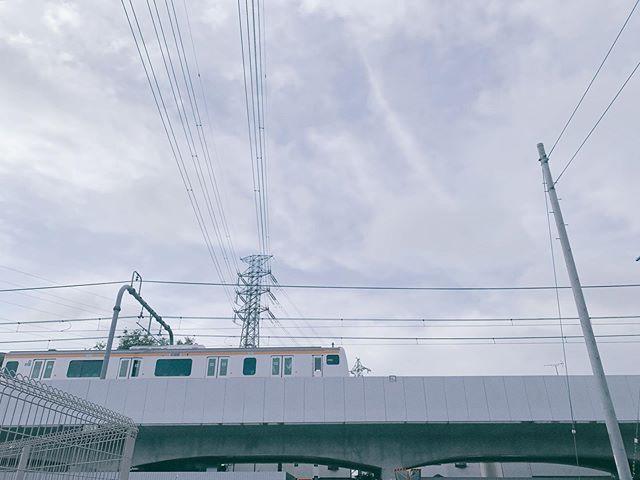 東京を東西に走る中央線の車両の画像。朝の空の下、高架の上を走っている。